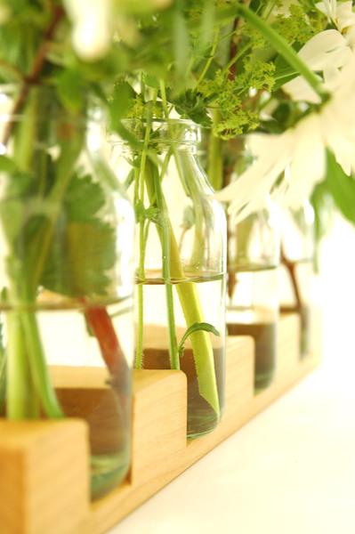 Blumenwiese mit Milchgläsern als Blumenvasen