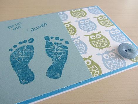 Babyfüße oder Babyhände mit Stempelfarbe auf Papier bringen