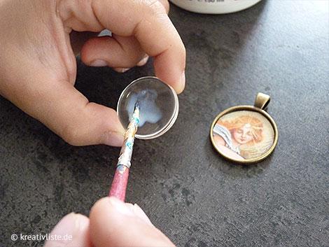 Transparentkleber wird sparsam auf das Cabochon gestrichen