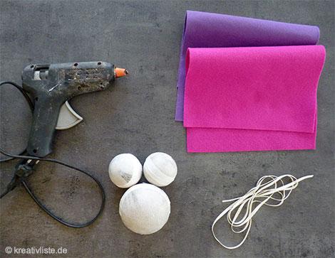 Neben einer Klebepistole benötigt man Filzplatten, eine Schere,  Kugeln zum Aufkleben und ein Band zum Hängen