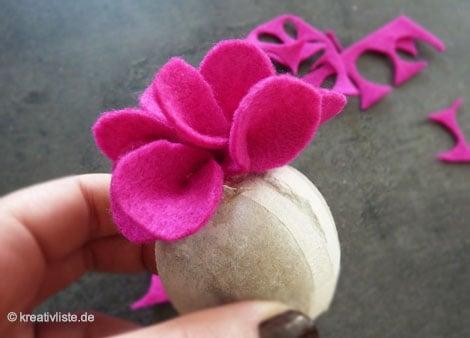 Die einzelnen Blütenblätter werden nun mit Heißkleber auf der Kugel befestigt
