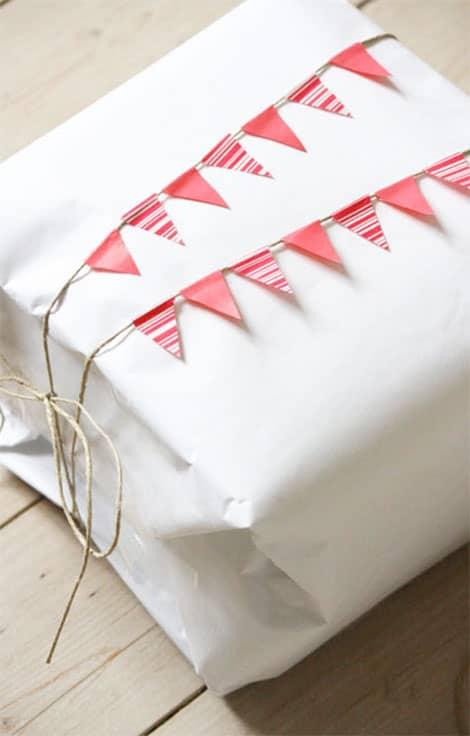 Eine Wimpelkette mit Masking Tape und Paketband ziert hier ein schlichtes Geschenk