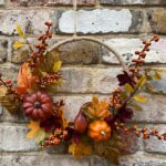 Zarter Herbstkranz mit Minikürbissen und Beeren auf einem Juteuntergrund